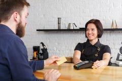 Lächelndes barista, das Zahlung vom Kunden am Zähler einer Kaffeestube nimmt stockfotos