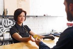 Lächelndes barista, das Zahlung vom Kunden am Zähler einer Kaffeestube nimmt lizenzfreie stockbilder