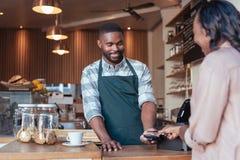 Lächelndes barista unter Verwendung nfc Technologie für eine Kunde ` s Zahlung Stockbilder