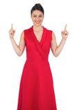 Lächelndes bezauberndes Modell im roten Kleid, das oben zeigt Stockbild