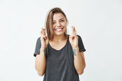 Lächelndes Blinzeln des jungen schönen emotionalen Mädchens, die Kamera betrachtend, die über weißem Hintergrund betet Lizenzfreies Stockfoto