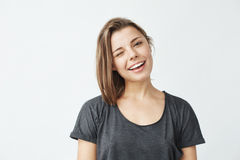 Lächelndes Blinzeln des netten jungen schönen Mädchens, Kamera über weißem Hintergrund betrachtend Lizenzfreie Stockfotografie