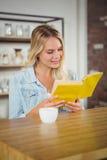 Lächelndes blonde Lesegelbes Buch Stockfotos