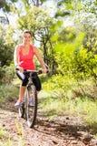 Lächelndes blondes Athletengebirgsradfahren Stockfotos