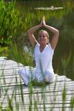 Lächelndes blondes betendes Yoga des Mädchens 20s, Wasserumwelt Lizenzfreie Stockbilder