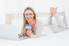 Lächelndes blondes Einkaufen online auf dem Bett Stockfoto