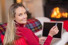 Lächelndes blondes Einkaufen online mit Laptop am Weihnachten Stockfotos