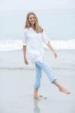 Lächelndes blondes Gehen durch das Meer und Betrachten der Kamera Lizenzfreie Stockfotos