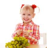 Lächelndes blondes Kind essen am Tisch Stockfotografie