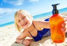 Lächelndes blondes Kind im Badeanzug auf der Küste, die Sonnenschutz zeigt Stockfotos