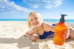 Lächelndes blondes Kind im Badeanzug auf der Küste, die Sonnenschutz zeigt Lizenzfreies Stockbild