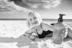 Lächelndes blondes Kind im Badeanzug auf der Küste, die Sonnenschutz zeigt Lizenzfreie Stockbilder