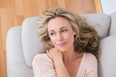 Lächelndes blondes Lügen auf dem Couchdenken Stockfoto