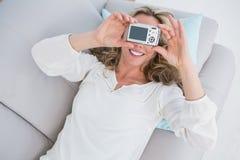 Lächelndes blondes Lügen auf der Couch, die ein selfie nimmt Lizenzfreie Stockfotografie