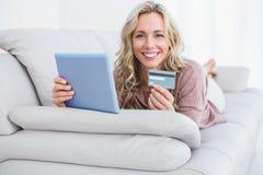 Lächelndes blondes Lügen auf der Couch, die online mit Tablette kauft Stockfoto