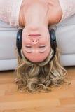 Lächelndes blondes Lügen auf hörender Musik der Couch Stockfotografie