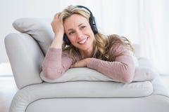 Lächelndes blondes Lügen auf hörender Musik der Couch Lizenzfreie Stockbilder