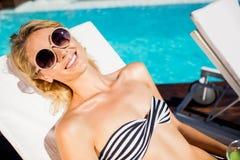 Lächelndes blondes Lügen auf Klappstuhl Lizenzfreie Stockfotos