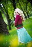Lächelndes blondes Mädchen über grünem Gras Lizenzfreie Stockfotos