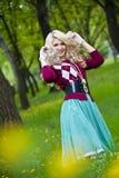 Lächelndes blondes Mädchen über grünem Gras Lizenzfreies Stockfoto