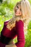 Lächelndes blondes Mädchen über grünem Gras Lizenzfreie Stockfotografie