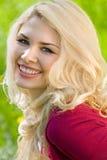 Lächelndes blondes Mädchen über grünem Gras Stockfoto