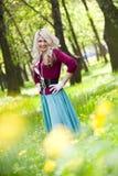 Lächelndes blondes Mädchen über grünem Gras Stockfotografie