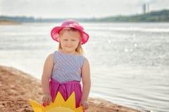 Lächelndes blondes Mädchen, das auf Flussbank, Nahaufnahme aufwirft Stockbilder