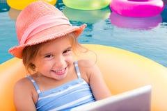 Lächelndes blondes Mädchen, das auf gelbes inneres Rohr schwimmt Stockfotografie