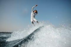 Lächelndes blondes Mädchen, das auf das grüne wakeboard auf den verbiegenden Knien springt stockfoto