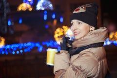 Lächelndes blondes Mädchen, das auf Hintergrund mit Lichtern auf dem St. steht Stockfotografie