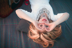 Lächelndes blondes Mädchen, das durch ihre Hände in Form von hea schaut Stockfotos