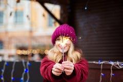 Lächelndes blondes Mädchen, das glühende Bengal-Lichter beim Christm hält Stockfotografie