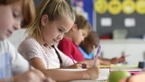 Lächelndes blondes Mädchen, das Klassenarbeit tut stock video