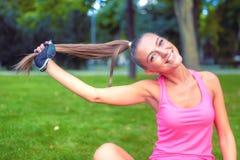 Lächelndes blondes Mädchen, das mit dem Haar beim Ausarbeiten im Park spielt Stockfotos