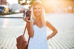 Lächelndes blondes Mädchen der Junge, das Retro- Kamera auf der Straße hält Stockfotos
