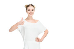 Lächelndes blondes Mädchen in der weißen Kleidung mit dem Daumen, der oben Kamera betrachtet Lizenzfreies Stockfoto