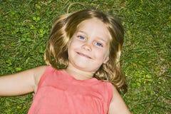 Lächelndes blondes Mädchen im Gras Lizenzfreies Stockfoto