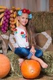 Lächelndes blondes Mädchen mit dem langen Haar in einem bunten ukrainischen Kranz und in gestickt, sitzt auf Heuschobern Herbstde lizenzfreies stockfoto