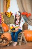 Lächelndes blondes Mädchen mit dem langen Haar in einem bunten ukrainischen Kranz und in gestickt, sitzt auf Heuschobern Herbstde lizenzfreie stockbilder