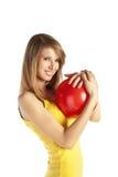 Lächelndes blondes Mädchen mit roter Kugel Stockfotos