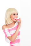 Lächelndes blondes Mädchen, welches das Plakat liest Stockfotos