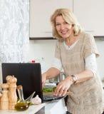 Lächelndes blondes reifes Frauenkochen Stockfoto