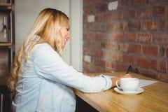 Lächelndes blondes Schreiben auf Blatt Papier Stockfoto