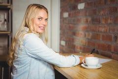 Lächelndes blondes Schreiben auf Blatt Papier Stockfotos