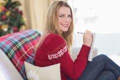 Lächelndes blondes Schreiben beim Sitzen auf dem Sofa Lizenzfreie Stockfotos