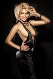 Lächelndes blondes sexy Mädchen, das tragendes schwarzes Kleid aufwirft Stockbilder