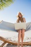 Lächelndes blondes Sitzen auf Hängematte unter Verwendung des Laptops Lizenzfreie Stockbilder