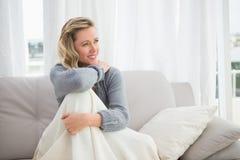 Lächelndes blondes Sitzen auf ihrem Couchdenken Lizenzfreies Stockfoto