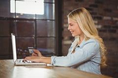Lächelndes blondes tuendes on-line-Einkaufen Stockbild